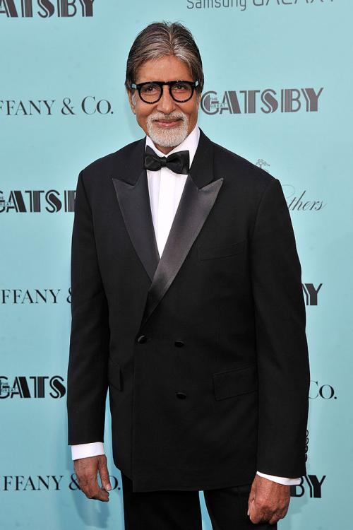 Amitabh Bachchan in a tux on red carpet.