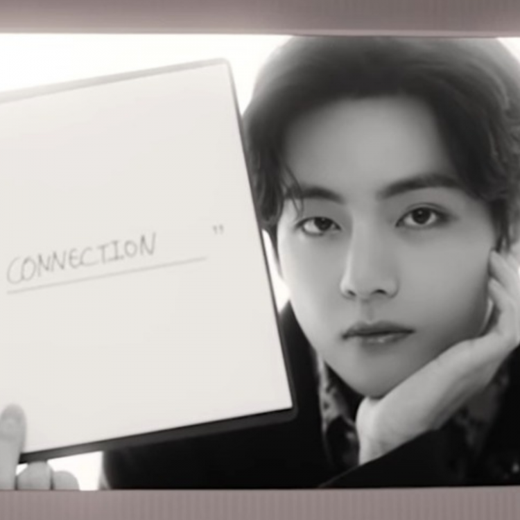 A still of BTS' V holding a 'I Believe In Connection' slate from Big Hit's What Do You Believe In video