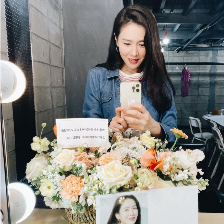 Actress Son Ye Jin taking a mirror selfie with the flower bouquet received as a gift