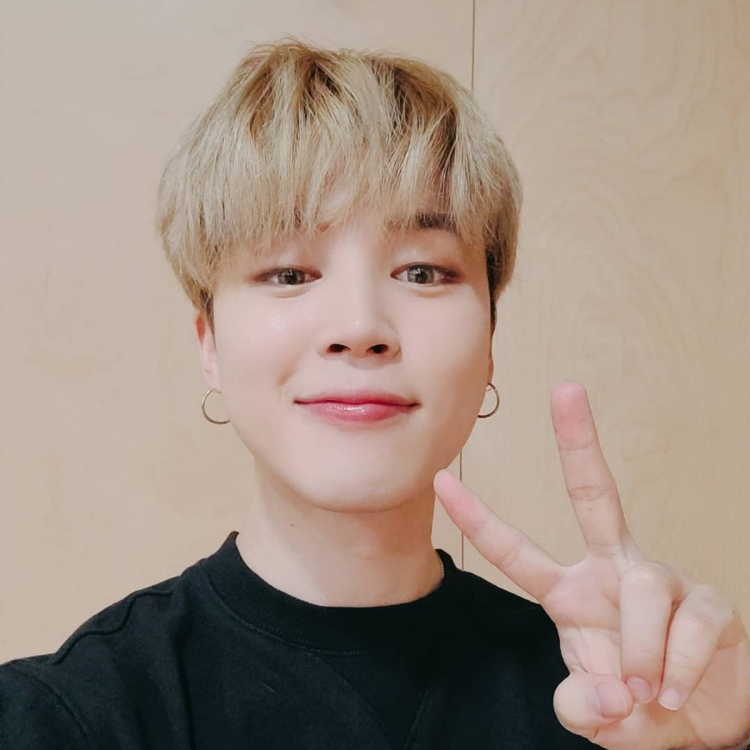 BTS' member Jimin clicking a selfie with a V-sign, wearing a black Tshirt