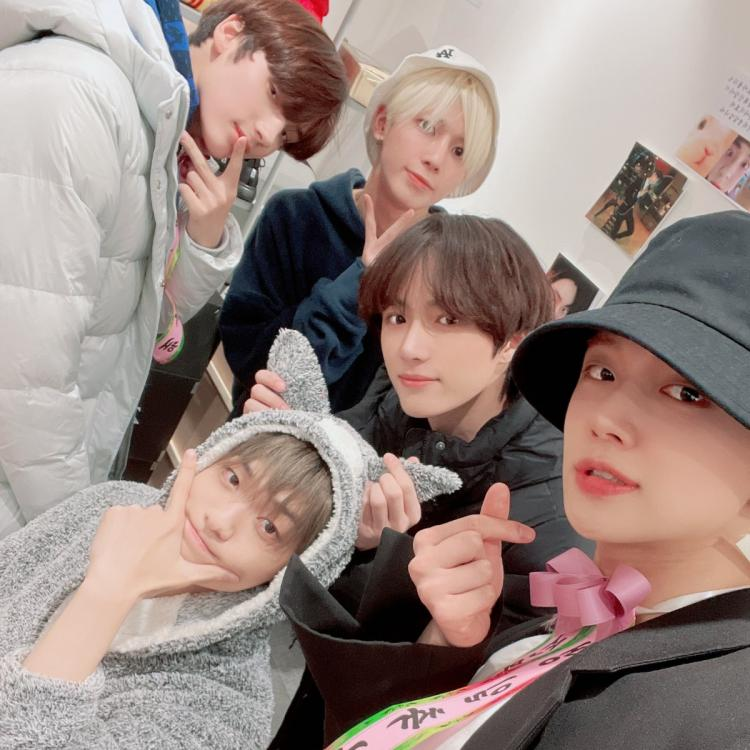 KPop group TXT members clicking a selfie