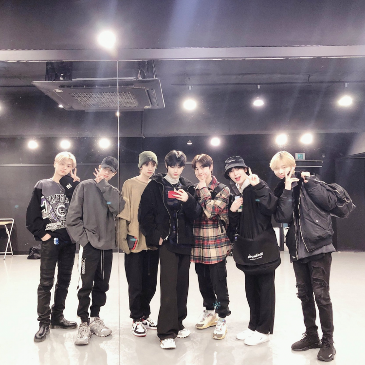 ENHYPEN group members taking a mirror selfie; announced comeback in April 2021