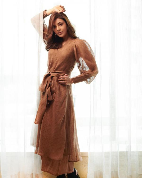 Kajal Aggarwal strikes a pose in a feminine tan dress which flatters her silhouette