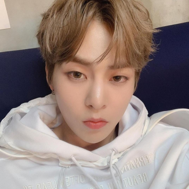 EXO's Xiumin poses for a selca in a comfy white hoodie, posted on Instagram