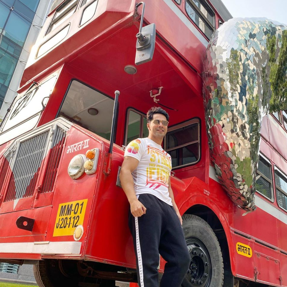 Varun Dhawan poses beside a red bus as he goes on a promotional spree for Street Dancer; See Pic